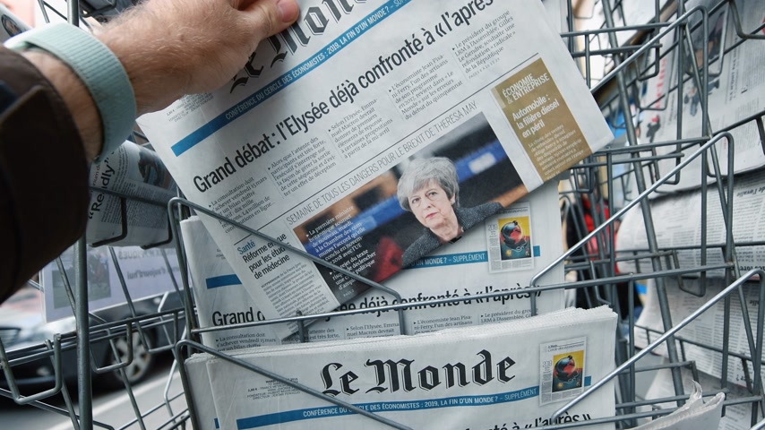 buy newspaper : Paris, France - Mar 12, 2019: Male hand taking from the newspaper stand French newspaper Le Monde featuring on the cover Theresa May and last deals about Brexit Stock Footage
