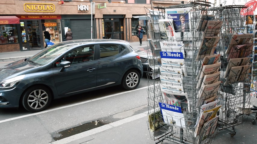 szemléltető : Paris, France - Mar 12, 2019: French press kiosk media stand with pedestrians walking and cars parked nearby journalism mass media distribution Stock mozgókép