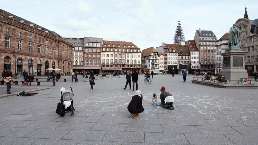 petite : Strasbourg, France - Mar 12, 2019: Wide image of central Place Kleber in Strasbourg on a sunny afternoon with peaceful people drawing with chalk flowers near General Kleber statue Stock Footage