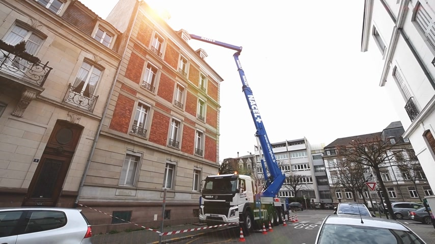 emel : Strasbourg, France - Dec 13, 2019: Sunlight flare over Volvo Truck FMx with new nacelle manipulator hydraulic lifter lifting cargo on roof of the luxury French building during repair construction