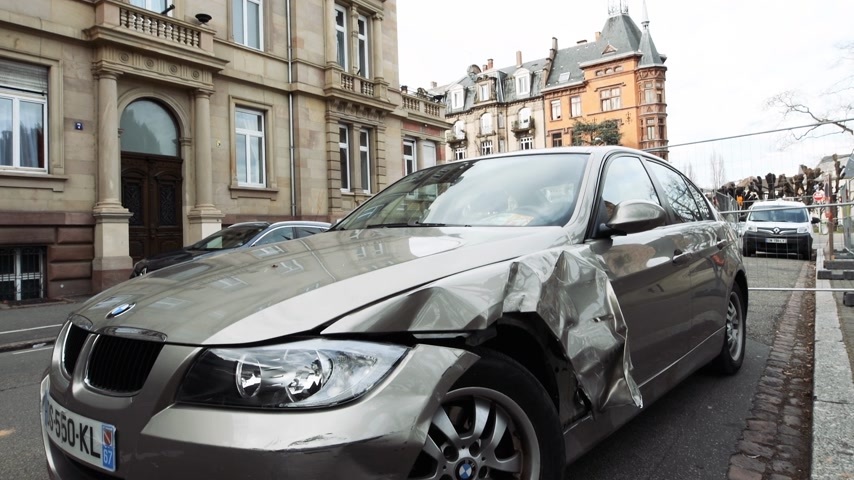 fender : Strasbourg, France - Mar 12, 2019: Tilt-down to luxury BMW German car parked on city street with damaged front by accident on the road