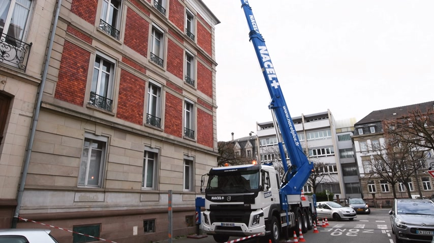 kladkostroj : Strasbourg, France - Dec 13, 2019: Volvo Truck FMx with new nacelle manipulator hydraulic lifter lifting cargo on roof of the luxury French building during repair construction Dostupné videozáznamy