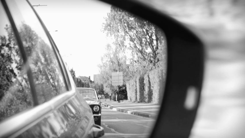 odrážející : NICE, FRANCE - CIRCA 2019: Cinematic black and white side view car mirror reflection of two-lane road in city with Ford Mustang convertible car following - scene to be used in movies, stories and other editorial needs