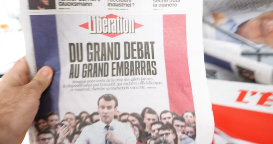 french media : Paris, France - Mar 15, 2019: Man shopping at press kiosk for Liberation French newspaper featuring French President Emmanuel Macron and Grand Debat title Stock Footage