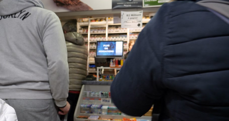 tabloid : Paris, France - Mar 15, 2019: People shopping in queue inside tobacco press kiosk buying newspapers, cigarettes and lotto tickets