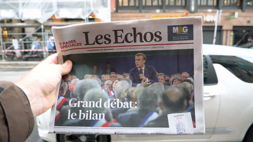 vita : Paris, France - Mar 15, 2019: Man hand holding against French city background Les Echos newspaper featuring Emmanuel macron President and Grand Debat news Great Debate - slow motion Stock mozgókép