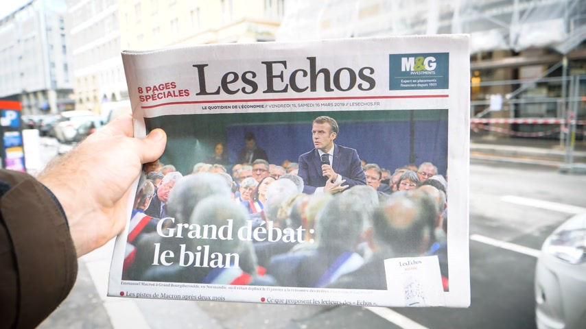 french president : Paris, France - Mar 15, 2019: Man hand holding against French city background Les Echos newspaper featuring Emmanuel macron President and Grand Debat news Great Debate - slow motion Stock Footage