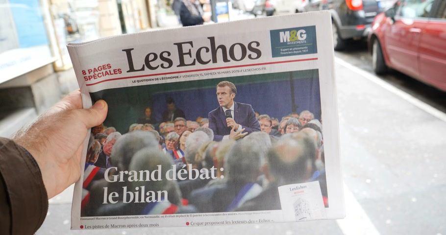 french media : Paris, France - Mar 15, 2019: Man hand holding against French city background Les Echos newspaper featuring Emmanuel macron President and Grand Debat news Great Debate