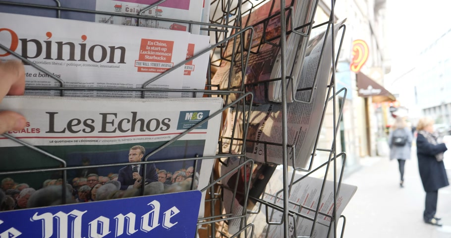 başkan : Paris, France - Mar 15, 2019: Man hand taking from kiosks Les Echos newspaper featuring Emmanuel Macron President and Grand Debat news Great Debate