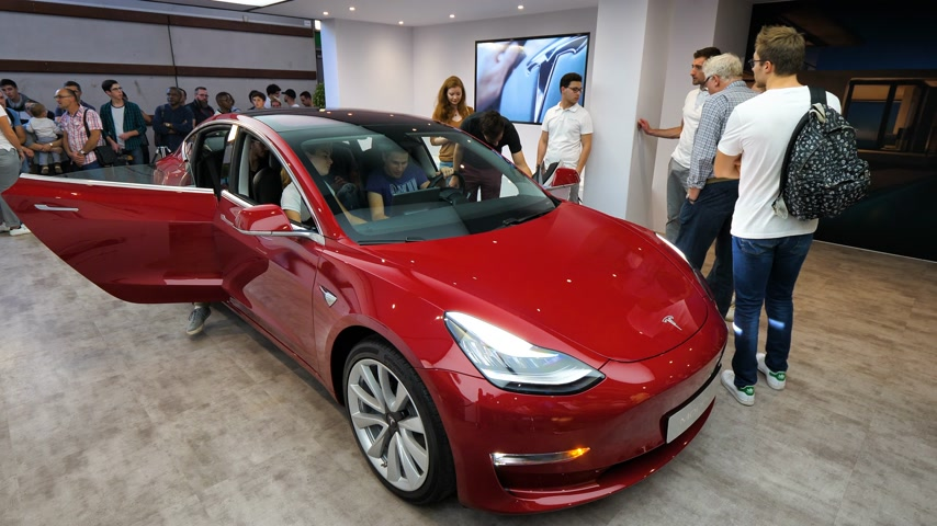 tesla car : PARIS, FRANCE - OCT 4, 2018: Customers and curious people admiring the new electric Tesla Model 3 at International car exhibition Mondial Paris Motor Show, model produced by US car maker Stock Footage