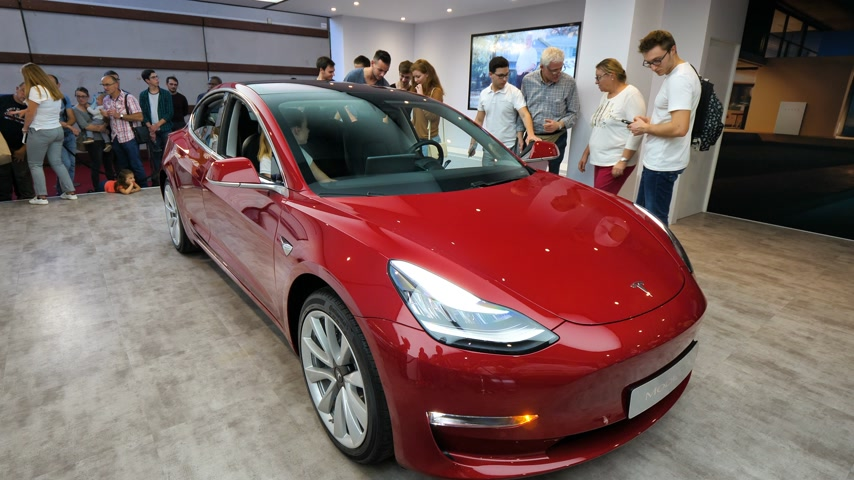 tesla car : PARIS, FRANCE - OCT 4, 2018: Senior man trying the new electric Tesla Model 3 at International car exhibition Mondial Paris Motor Show, model produced by US car maker Stock Footage