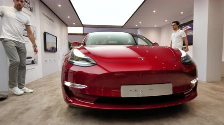 sprzedawca : PARIS, FRANCE - OCT 4, 2018: Front view of new electric Tesla Model 3 at International car exhibition Mondial Paris Motor Show, model produced by US car maker - dealers men presentation