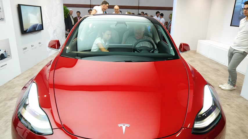 sala de exposição : PARIS, FRANCE - OCT 4, 2018: Cinematic newsworthy footage young woman explaining to senior man the features advantages of new electric red Tesla Model 3 made in US at car motor show Stock Footage