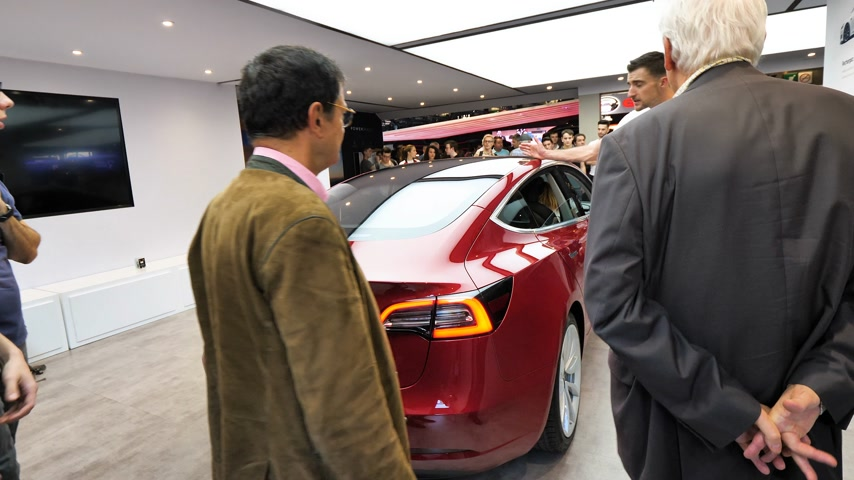 sprzedawca : PARIS, FRANCE - OCT 4, 2018: Customers and curious people being instructed about the new electric Tesla Model 3 at International car exhibition Mondial Paris Motor Show, model produced by US car maker Wideo