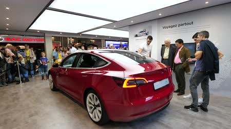 tesla car : PARIS, FRANCE - OCT 4 2018: Sales person presenting to customers people admiring the new electric Tesla Model 3 at International car exhibition Mondial Paris Motor Show, model produced by US car maker