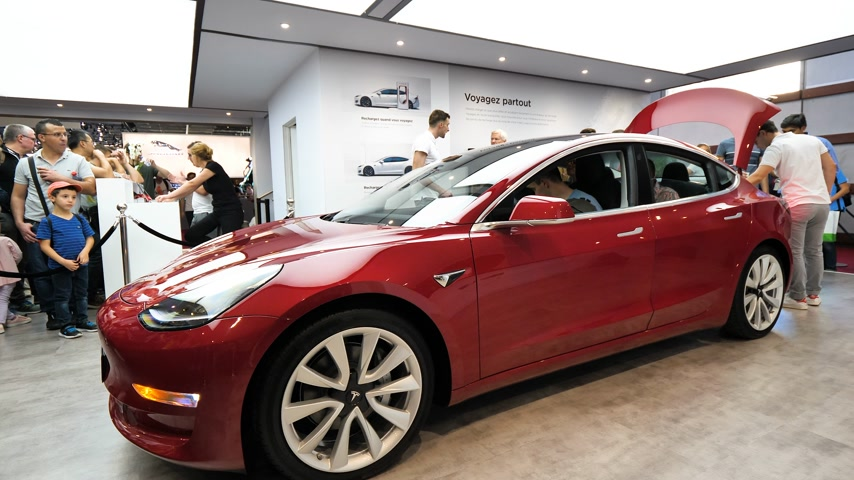 tesla car : PARIS, FRANCE - OCT 4 2018: Side view of sales person presenting to customers people admiring the new electric Tesla Model 3 at International car exhibition show, model produced by US car maker