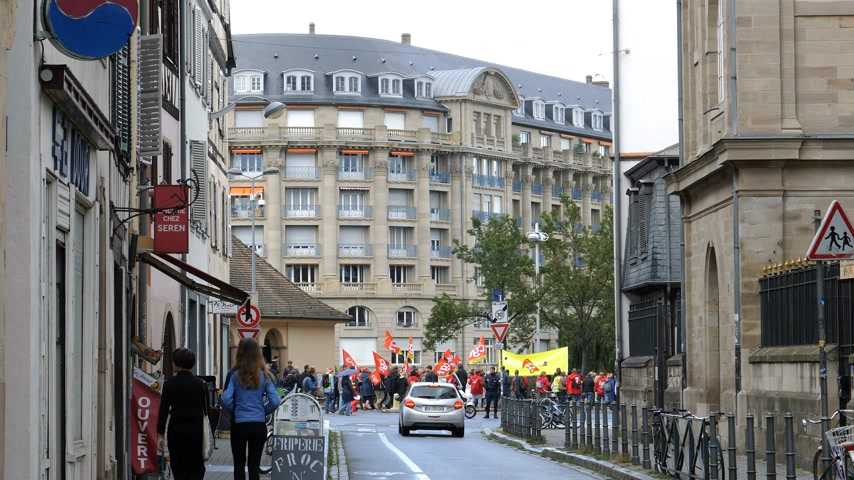 nationwide protest : Strasbourg, France - Sep 12, 2017: ESCA luxury building in central Strasbourg and protesters with CGT red flags at political march during a French Nationwide day of protest