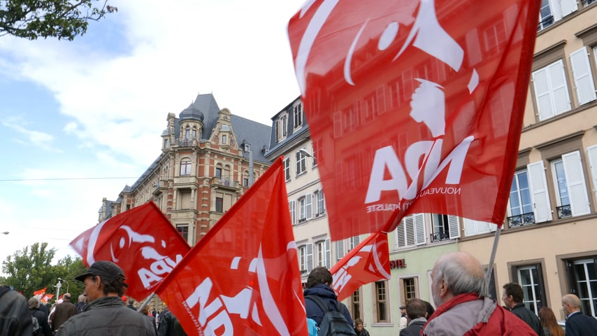 szakszervezet : Strasbourg, France - Sep 12, 2017: NPA New Anticapitalist Party nouveau parti anticapitaliste maintenant flags people at political march during a French Nationwide day of protest against labor reforms Stock mozgókép