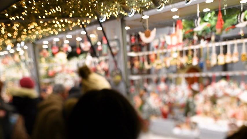kardan adam : Strasbourg, France - Circa 2018: Tilt-shift lens over Strasbourg annual Christmas winter market tourists and locals shopping for handmade toys at market stall Stok Video