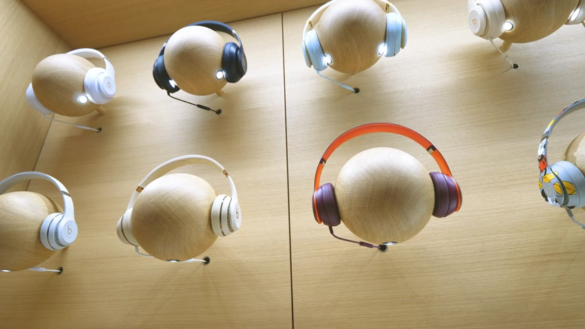 apple computers : Paris, France - Circa 2019: Slow pan over multiple Beats Apple products headphones on mannequin heads are displayed inside the new Apple Store Champs-Elysees largest French store located in the heart of the capital