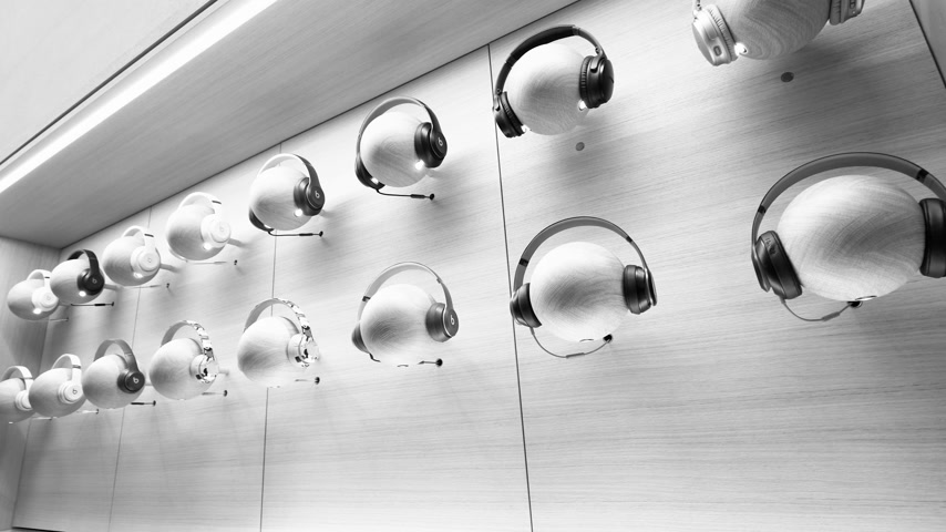 champs elysee : Paris, France - Circa 2019: Beats Apple products headphones on mannequin heads are displayed inside the new Apple Store Champs-Elysees largest French store - black and white footage