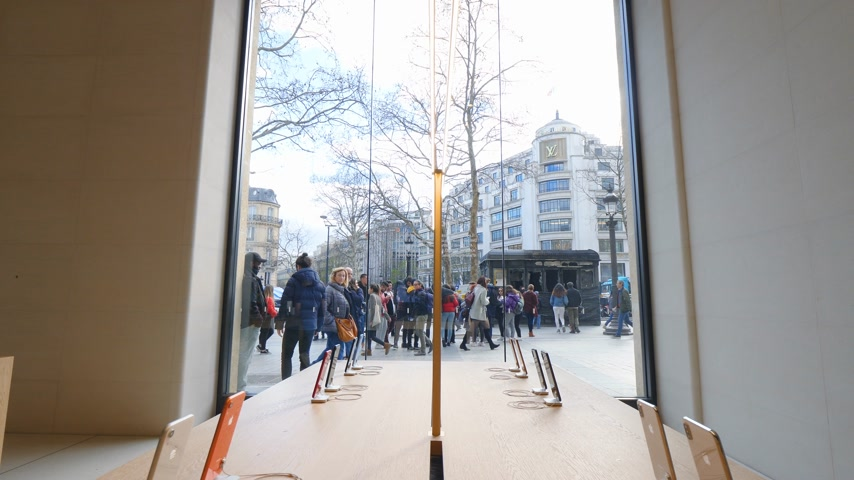 champs elysee : Paris, France - Circa 2019: Apple iPhone XS smartphones telephones inside the new Apple Store Champs-Elysees with Louis Vuitton flagship store and burnt kiosk after Yellow Vests protest Stock Footage