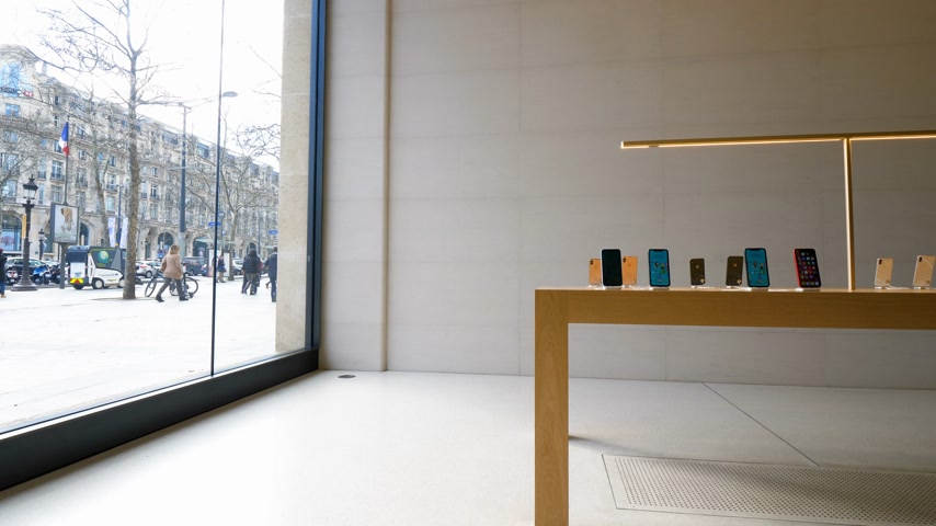 champs elysee : Paris, France - Circa 2019: Apple iPhone XS smartphones displayed inside the new Apple Store Champs-Elysees largest French store located in the heart of the capital with customers walking boulevard Stock Footage