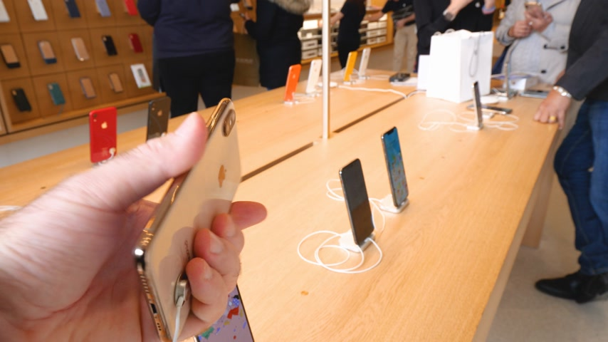 apple sign : Paris, France - Circa 2019: Apple iPhone XS gold smartphone in man hand inside new Apple Store Champs-Elysees largest French store located in the heart of the capital - apps icons fashion Stock Footage
