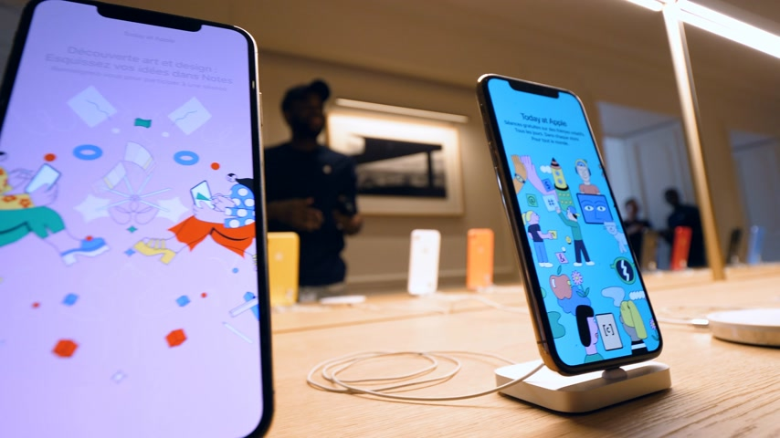 champs elysee : Paris, France - Circa 2019: Steadicam motion over iPhone XS smartphone - Apple products displayed inside the new Apple Store Champs-Elysees largest French store located in the heart of the capital Stock Footage