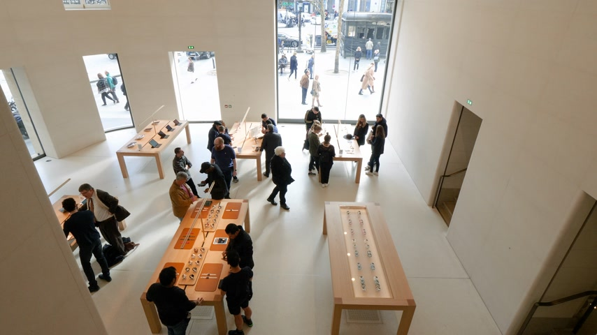 champs elysee : Paris, France - Circa 2019: Aerial view of customers admiring Apple iPhone Watch Tablet iPad products displayed inside the new Apple Store Champs-Elysees with iconic boulevard seen through big window