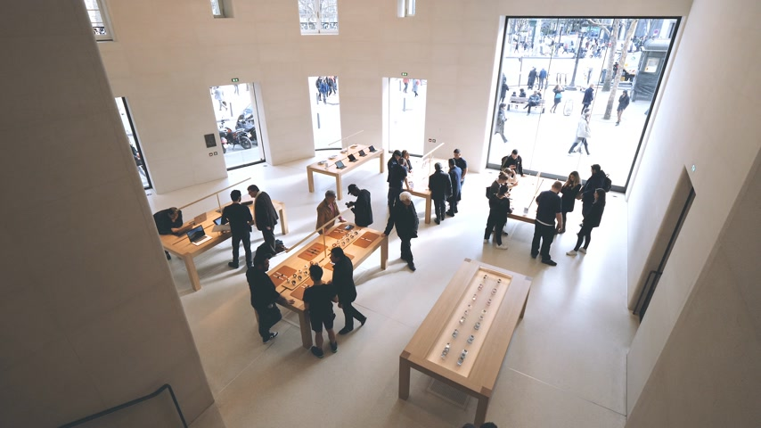 interior : Paris, France - Circa 2019: Aerial view of customers admiring Apple iPhone Watch Tablet iPad products displayed inside the new Apple Store Champs-Elysees slow motion 4K