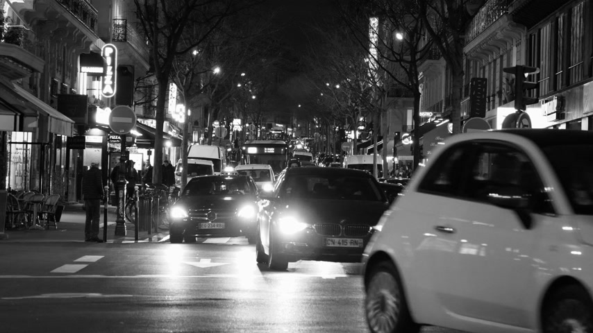 homeopático : Paris, France - Circa 2019: Typical French street in Paris with cars taxi commuters pedestrians at night commuting going home, restaurants sightseeing on a Friday night black and white Stock Footage