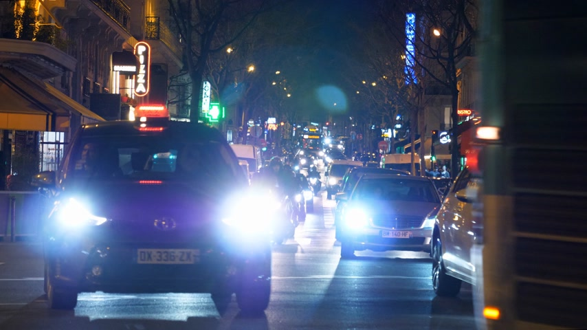 homeopático : Paris, France - Circa 2019: Paris public transportation bus on typical French street in Paris with cars taxi commuters pedestrians at night commuting going home, restaurants sightseeing Friday night Stock Footage