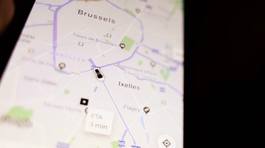talep : Brussels, Belgium - Circa 2019: Man POV holding iPhone smartphone running UBER peer-to-peer ridesharing app following trip share my trip during a ride map of the city with path