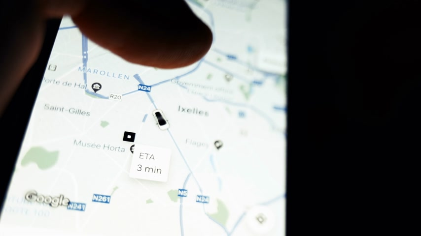 csökken : Brussels, Belgium - Circa 2019: Man POV holding iPhone smartphone running UBER peer-to-peer ridesharing app following trip share my trip during a ride Ixelles neighborhood central Brussels zoom on map