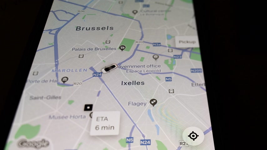 talep : Brussels, Belgium - Circa 2019: Man POV holding iPhone smartphone running UBER peer-to-peer ridesharing app following car icon on map trip share my trip during a ride on city map