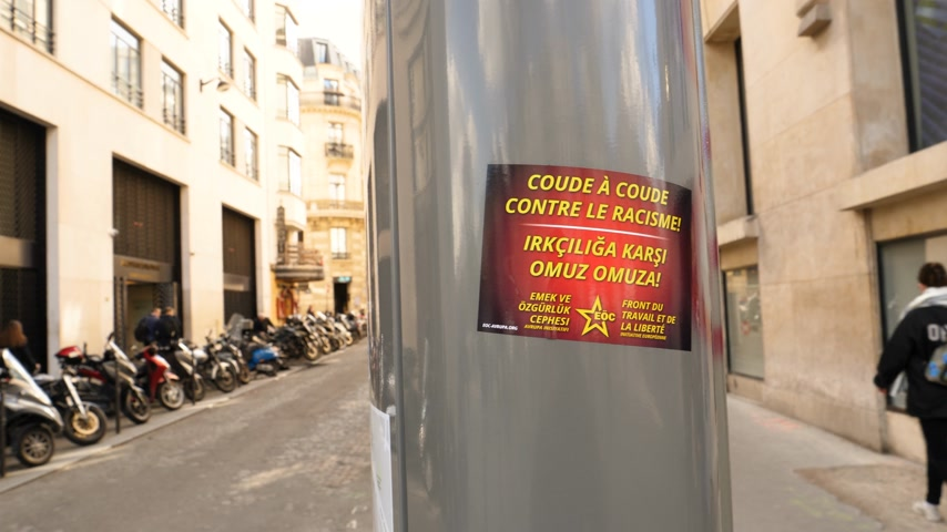 肘 : Paris, France - Circa 2019: Sticker on light pole in central Paris near Champs Elysees showing Coude a coude contre le racisme translated as Elbow next elbow against racism by Front du travail