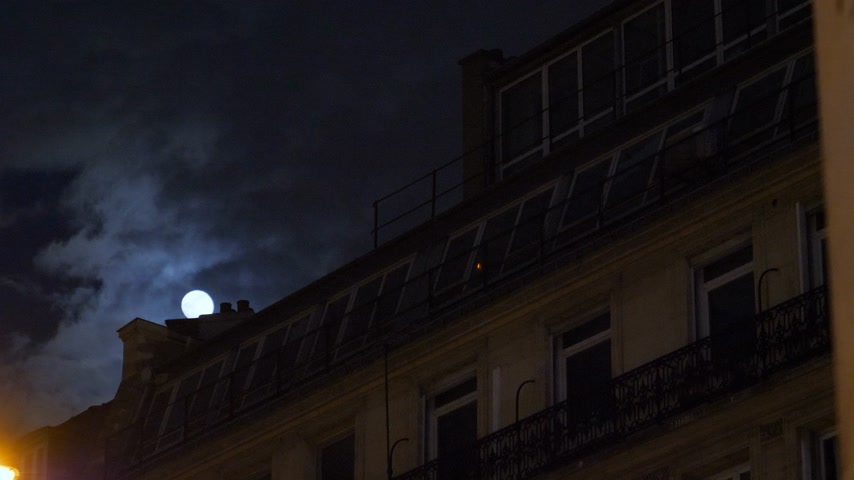 baixo : Beautiful full moon over Parisian Hausmannian building mansard roof on Champs-Elysees at night with beautiful columns on the balconies 4K UHD footage for film and series Vídeos