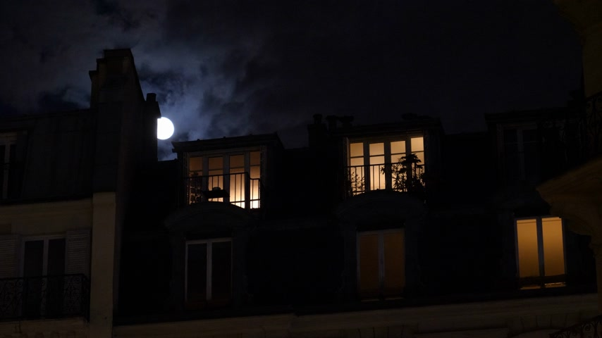 grotesque : Beautiful full moon over Parisian Hausmannian building on Champs-Elysees at night with beautiful mansard roof illuminated balconies logia windows 4K UHD footage for film and series