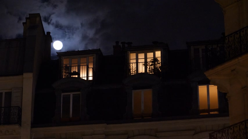 champs elysee : Beautiful full moon over Parisian Hausmannian building on Champs-Elysees at night with male silhouette walking inside apartment windows 4K UHD footage