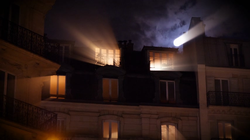 Radiating iridiscent light beams from beautiful full moon over Parisian Hausmannian building on Champs-Elysees at night with mansard roof balconies 4K UHD footage for film and series