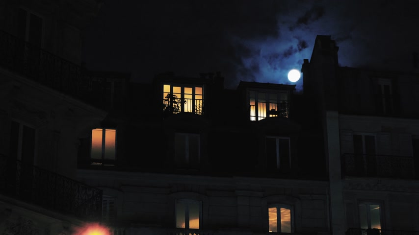 Male silhouette inside Parisian Hausmannian building on Champs-Elysees at night with beautiful full-moon 4K UHD footage for film and series