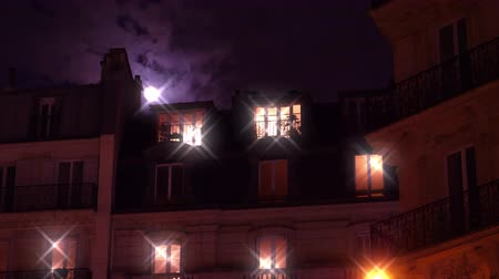 grotesque : Beautiful full moon over Parisian Hausmannian building on Champs-Elysees at night with beautiful star filter from light sources with male people silhouette inside the building