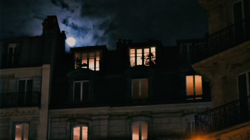 grotesque : Zoom out from beautiful full moon over Parisian Hausmannian building on Champs-Elysees at night with beautiful columns on the balconies 4K UHD footage for film and series