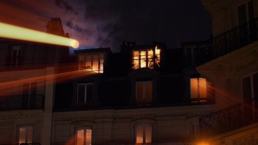 série : Radiating iridiscent light beams from beautiful full moon over Parisian Hausmannian building on Champs-Elysees at night with mansard roof balconies 4K UHD footage for film and series