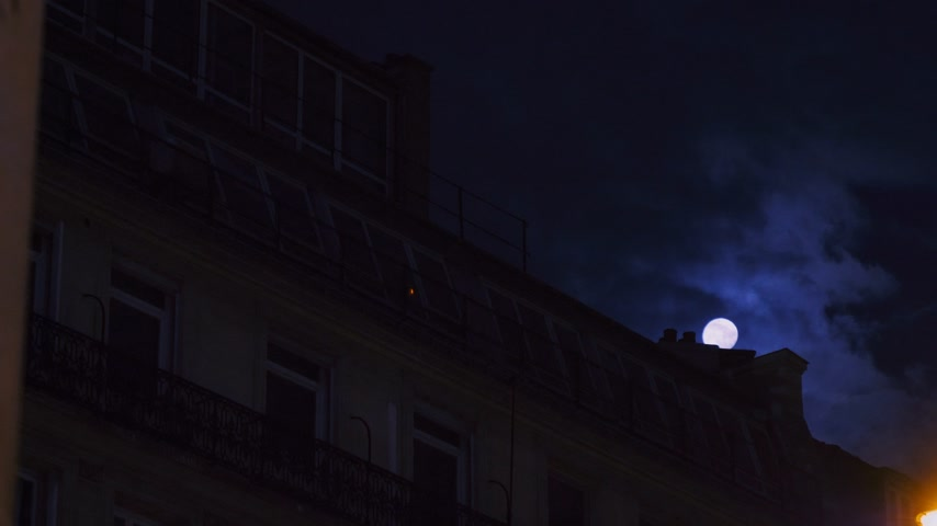 grotesque : Beautiful full moon over Parisian Hausmannian mansard roof on Champs-Elysees at night with beautiful columns on the balconies 4K UHD footage for film and series