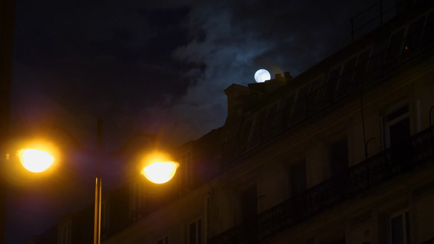 holdfény : Beautiful full moon over Parisian Hausmannian building on Champs-Elysees at night with beautiful Gambrel mansard roof 4K UHD footage for film and series Stock mozgókép