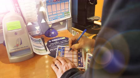 játék : Paris, France - 29 Mar 2019: Sunlight flare over senior male hands marking numbers on EuroMillions ticket inside Tabaco press kiosk hoping to win the big jackpot of 10000000 millions euros