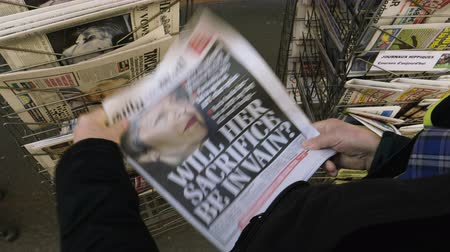 latest : Paris, France - 29 Mar 2019: Newspaper stand kiosk selling press with senior male hand buying latest Daily Mail UK press featuring Theresa may PM on front cover will her sacrifice be in vain