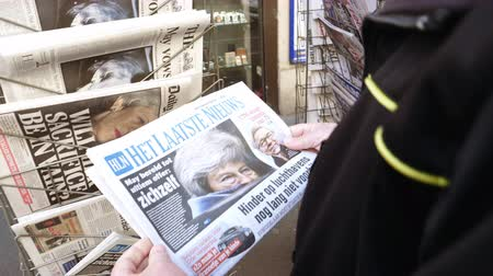 ヘッドライン : Paris, France - 29 Mar 2019: Newspaper stand kiosk selling press with senior male hand buying latest Het Laatste Nieuws Dutch press featuring Theresa May Prime Minister Brexit news on front cover 動画素材